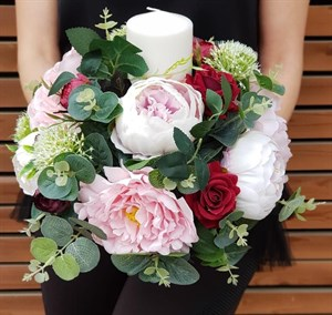 Композиция из декоративных цветов со свечей